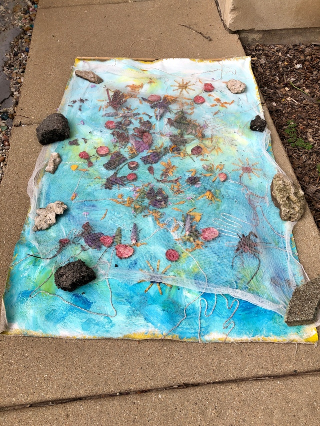 Weathered Art Fourth Location - front entrance sidewalk - flower petals under cheesecloth, rain on it's way.
